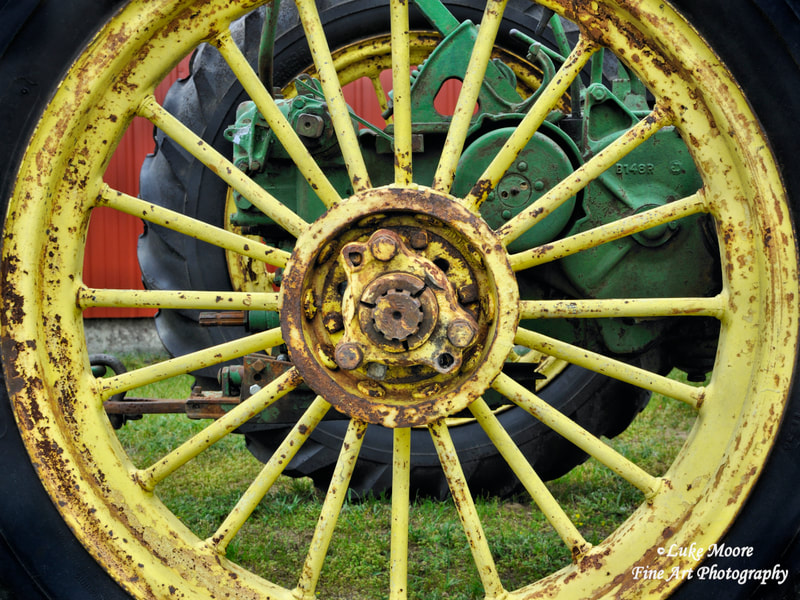 Antique John Deere tractor wheel and tractor parts with the signature yellow and green color scheme. I believe this is a John Deere Unstyled Model B tractor. Rustic farmhouse tractor photography and fine art abstract photography by Luke Moore. #JohnDeere