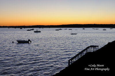 A peaceful July sunset over scenic Lewis Bay in West Yarmouth, Massachusetts, MA, 02673. Quintessential, summertime photograph of Cape Cod during the peak of the summer season. The boats are all moored in the harbor as the sun dips well below the horizon. Hyannis Port is also part of the silhouetted horizon. Cape Cod Prints and Wall Decor.