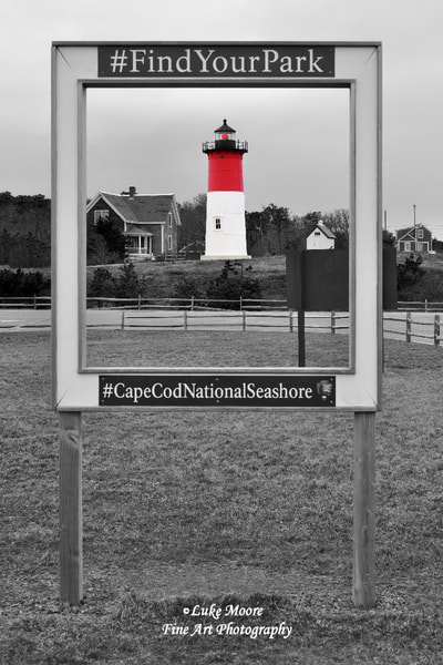 "A vintage style, black and white, seascape photograph of Nauset Beach Light in Eastham, Massachusetts, Cape Cod. In this lighthouse print, Nauset Lighthouse is framed by a Cape Cod National Seashore sign displaying hashtags. The lighthouse is brought to life with some selective color in this monochrome image. I waited for the red beacon to flash and I took the photo. To the left of the lighthouse you can see the historical lightkeeper's home, and to the right you can also see the little, white, oil house. ""Nauset Light Monochrome with Colorful Lighthouse"" landscape & nautical photography by Luke Moore. #CapeCodNationalSeashore #FindYourPark"