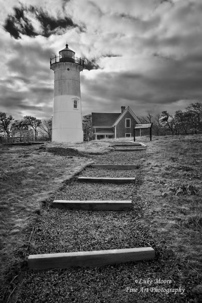 """Nauset Light Infrared"" fine art photography and art prints by Luke Moore. I pulled out my infrared camera to capture Nauset Beach Light on a mostly cloudy day in March. I wanted to express some character and begin to tell a story through this Nauset Lighthouse photograph. Infrared photography lends itself very well to creating a surreal, storytelling environment. I can't help but wonder how many shipwrecks and tragedies this lighthouse witnessed and/or helped to prevent.  Completed in 1838, Nauset Beach Lighthouse Station (The Three Sisters) was the first lighthouse station for Eastham, Massachusetts in Cape Cod. The Three Sisters consisted of three 15-foot brick towers each with a light on top. In 1892, these three towers were replaced with wooden towers and moved back from the eroding coastline. In 1911, more erosion caused one of the towers to be moved back again and two to be sold at auction. In 1923, the wooden lighthouse was retired and a new lighthouse was commissioned. The present day lighthouse is one of the towers from Chatham Light in Chatham, MA and was moved to Eastham in 1923. The Nauset Lighthouse has since been moved back several times due to dune erosion. For more historical information please visit the Nauset Light Preservation Society website."