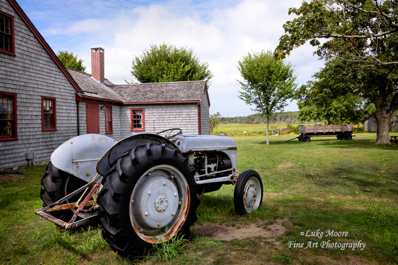 A vintage Ford tractor adds country flair to a charming New England landscape. This Massachusetts landscape incorporates both farmhouse and coastal themes. Country life landscapes and farmhouse decor by Luke Moore.