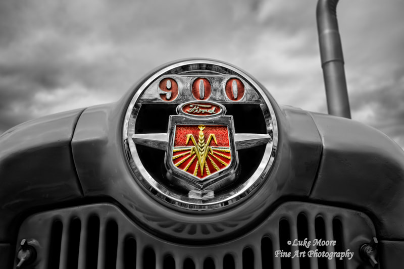 A vintage 1956 Ford 950 tractor, presented in dramatic black and white with selective color for the tractor grille nameplate. This Ford tractor Series 900 is read for more New England harvesting and farm duties. The Ford 950 was a row crop tractor made from 1954 to 1957. Tractor prints and industrial farm decor by Luke Moore