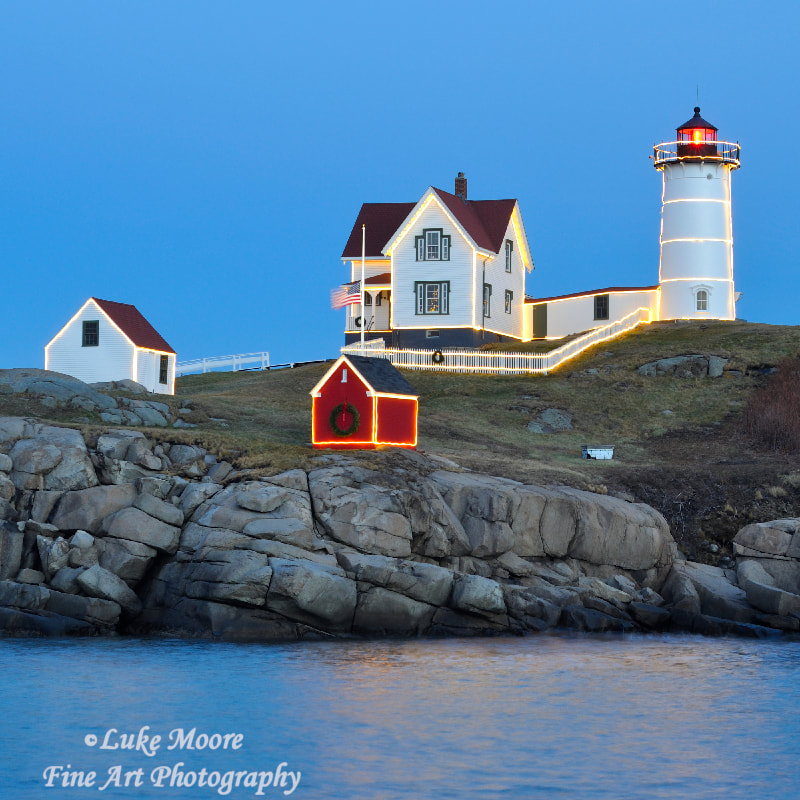 A lovely afternoon on a warm December day at the Nubble Lighthouse in York, Maine, New England. The sun is setting and the holiday Christmas lights are shining brightly. The red beacon of Cape Neddick Light flashes out towards the Atlantic Ocean and towards the mainland.