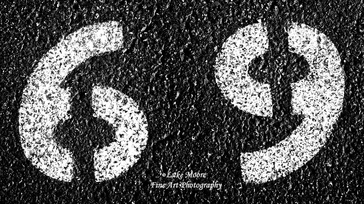 PictureA black and white, gritty photograph of a 69 painted on the pavement in a parking space. Abstract, number, and urban photography with symbolic roots.