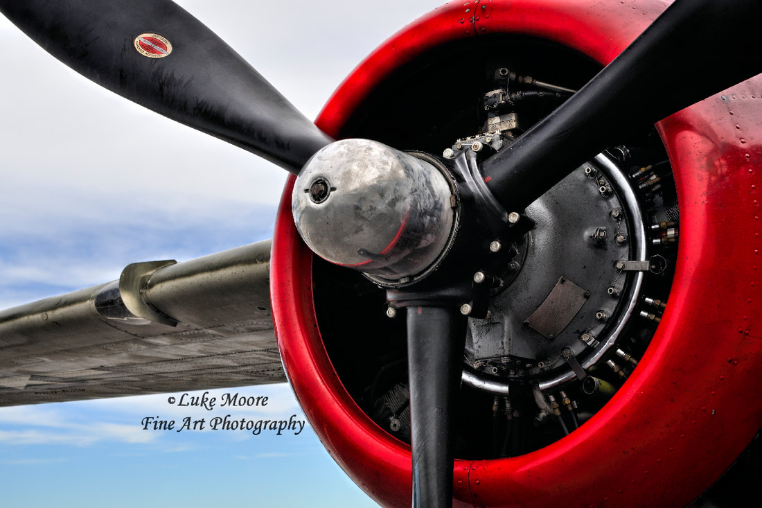 A bright red engine and propeller on a vintage World War ll bomber plane. This radial engine belongs to an old North America B-25 Mitchell aircraft. An abstract feel with a blue sky story to tell. This vintage aircraft was instrumental in WWll and during the four decades that followed. The Sky's the Limit - propeller plane print by Luke Moore.