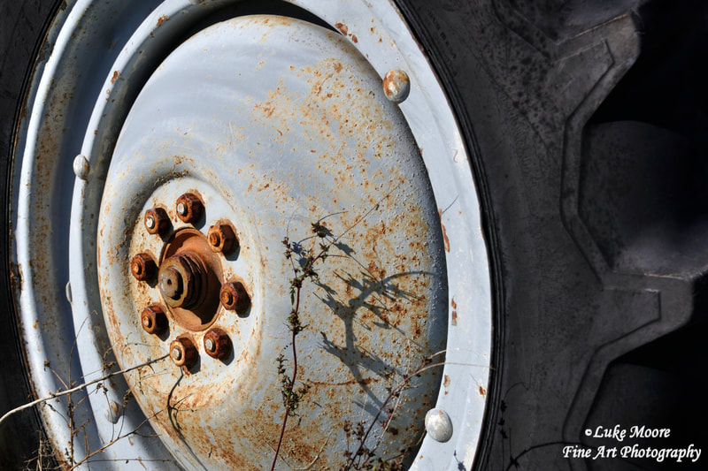Vintage Ford tractor wheel with rusty lug nuts and black rubber tire lugs.  New England tractor prints and tractor art by Luke Moore.