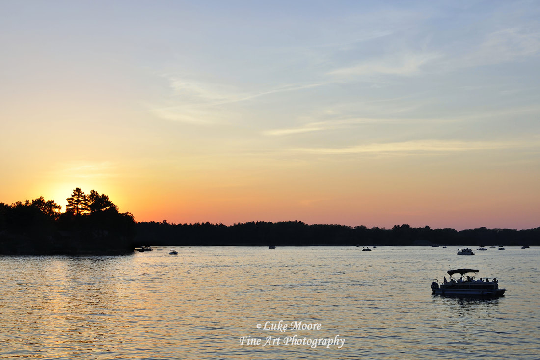 PictureWebster Lake sunset before the Independence Day fireworks on June 30th, 2018. The last rays of sunlight illuminate the sky as the boats anchor for the July 4th fireworks show. From this vantage point Memorial Beach starts in the rightmost part of this landscape photograph. Webster Lake in Webster, Massachusetts, MA is known by a few other names including Lake Chaubunagungamaug and Lake Chargoggagoggmanchauggagoggchaubunagung